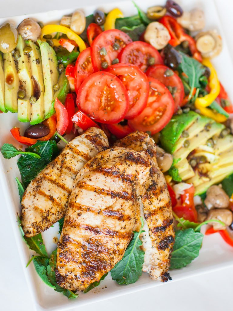 marinated grilled chicken over mediterranean salad with avocado