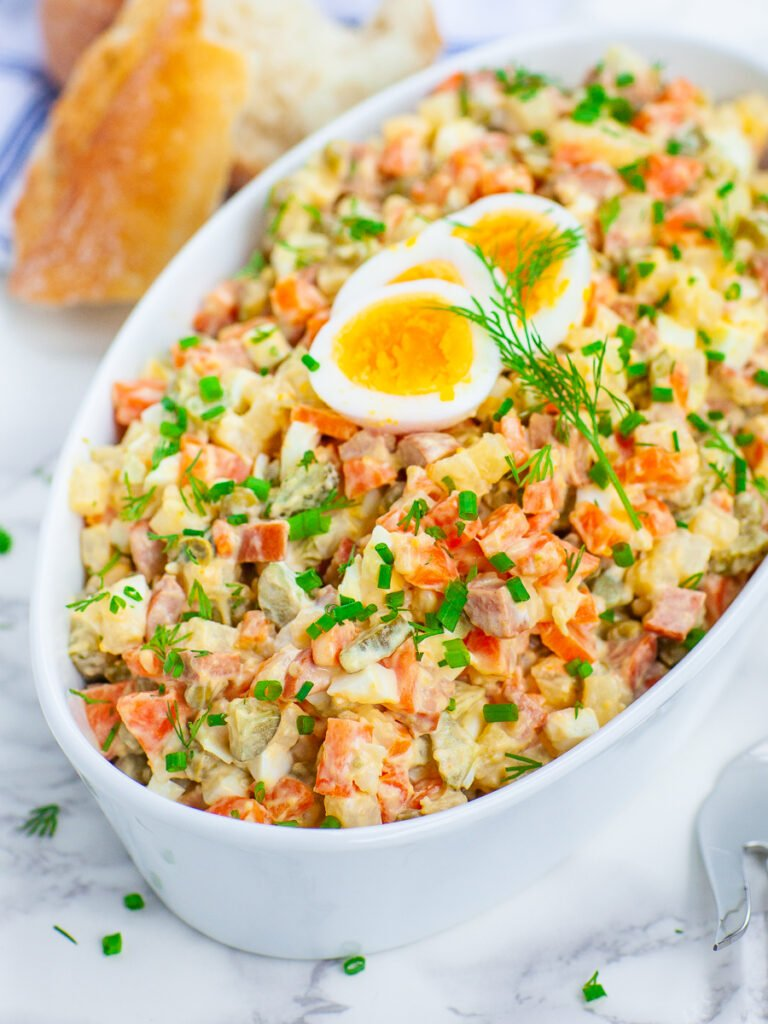 Olivier Russian Potato Salad Recipe topped with dill and hard boiled eggs
