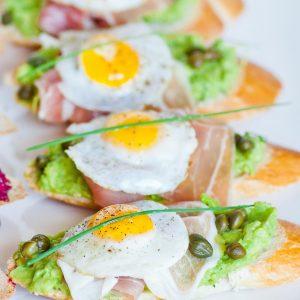 quail egg avocado toast with prosciutto