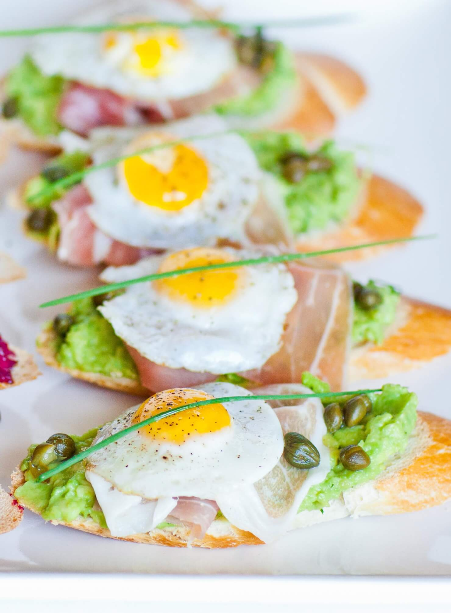 quail egg avocado toast with prosciutto