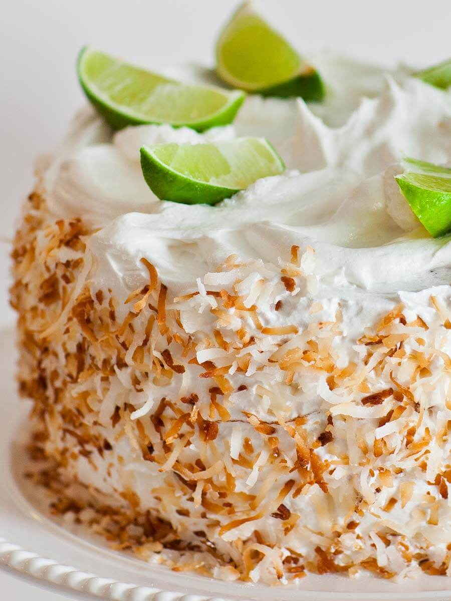 coconut lime cake with meringue frosting, toasted coconut and fresh limes