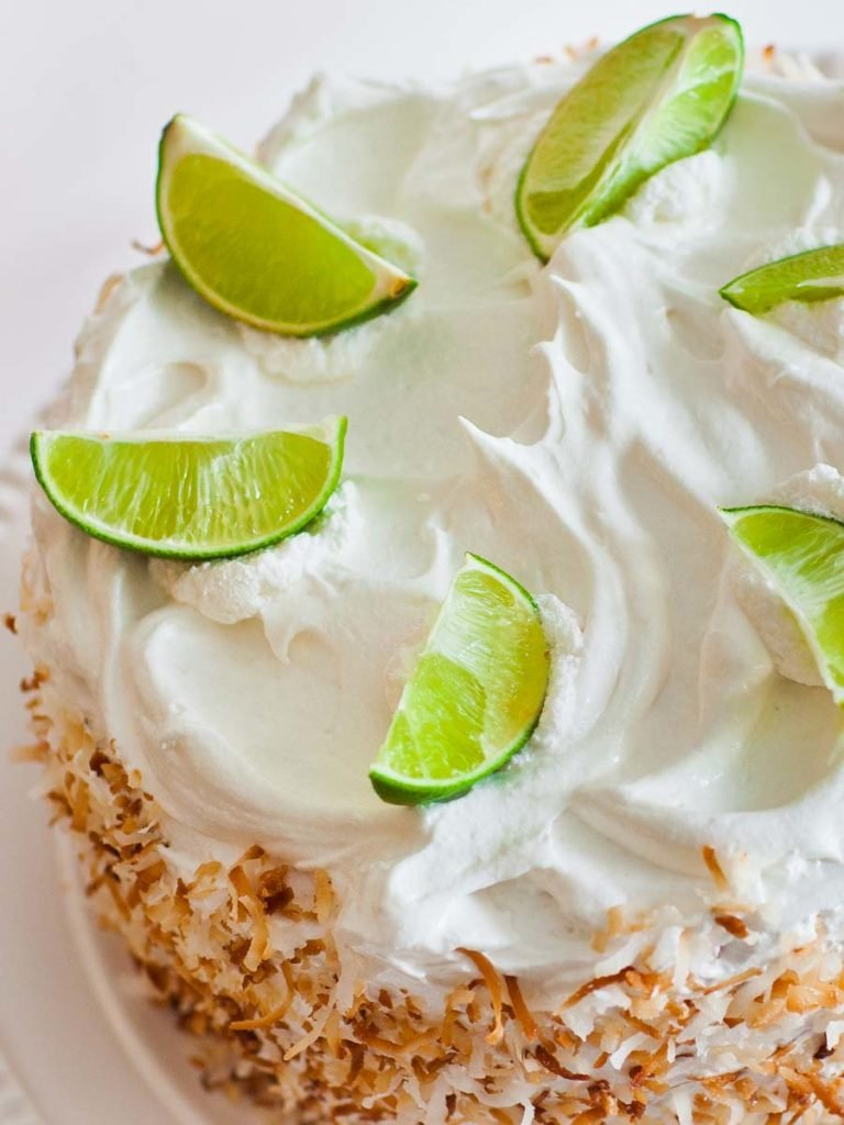 coconut lime cake topped with toasted coconut and lime wedges