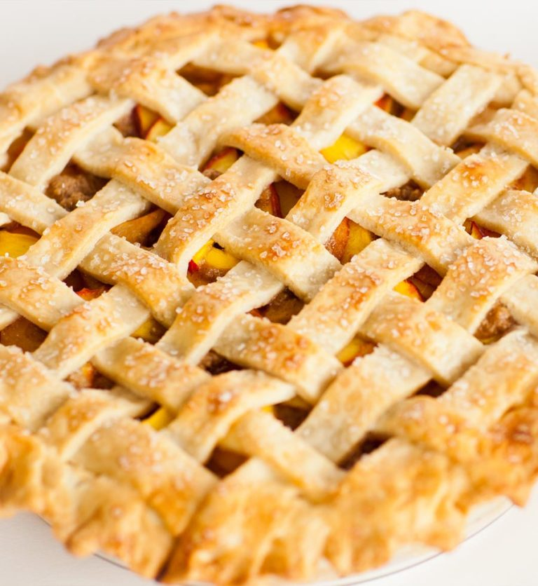 classic peach pie with lattice top and sugar crystals