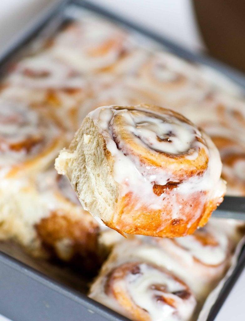 glazed cinnamon roll on spatula over pan of rolls