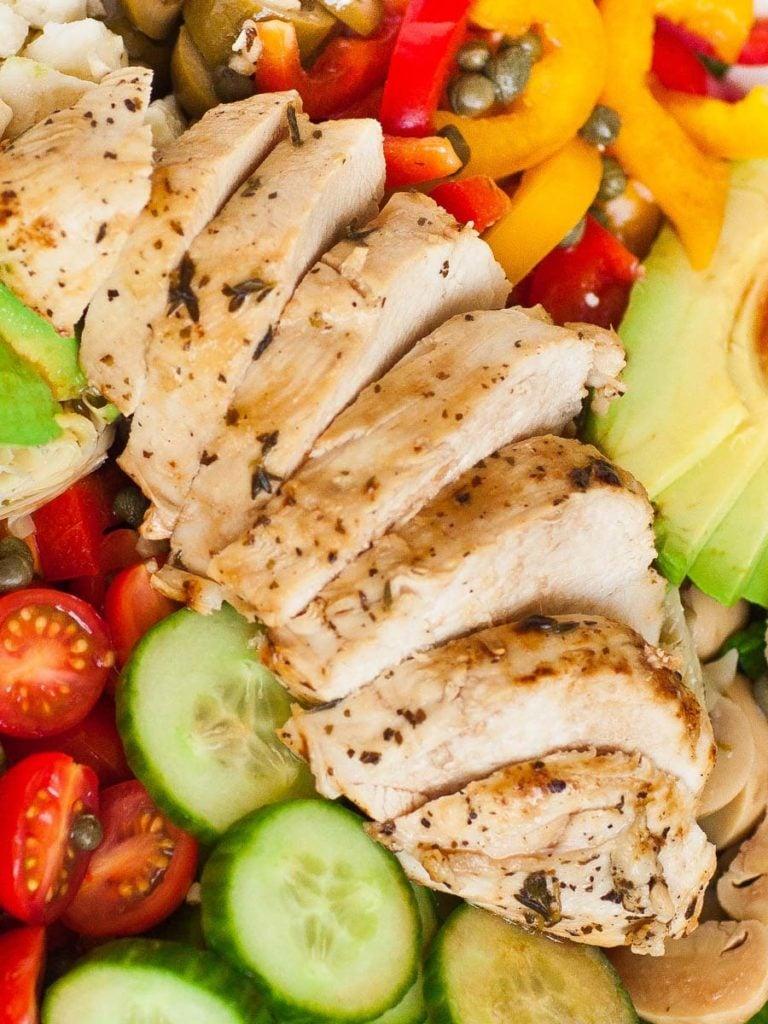 sliced italian chicken over italian salad
