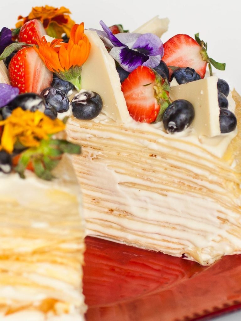 white chocolate crepe cake with whipped cream filling and edible flowers