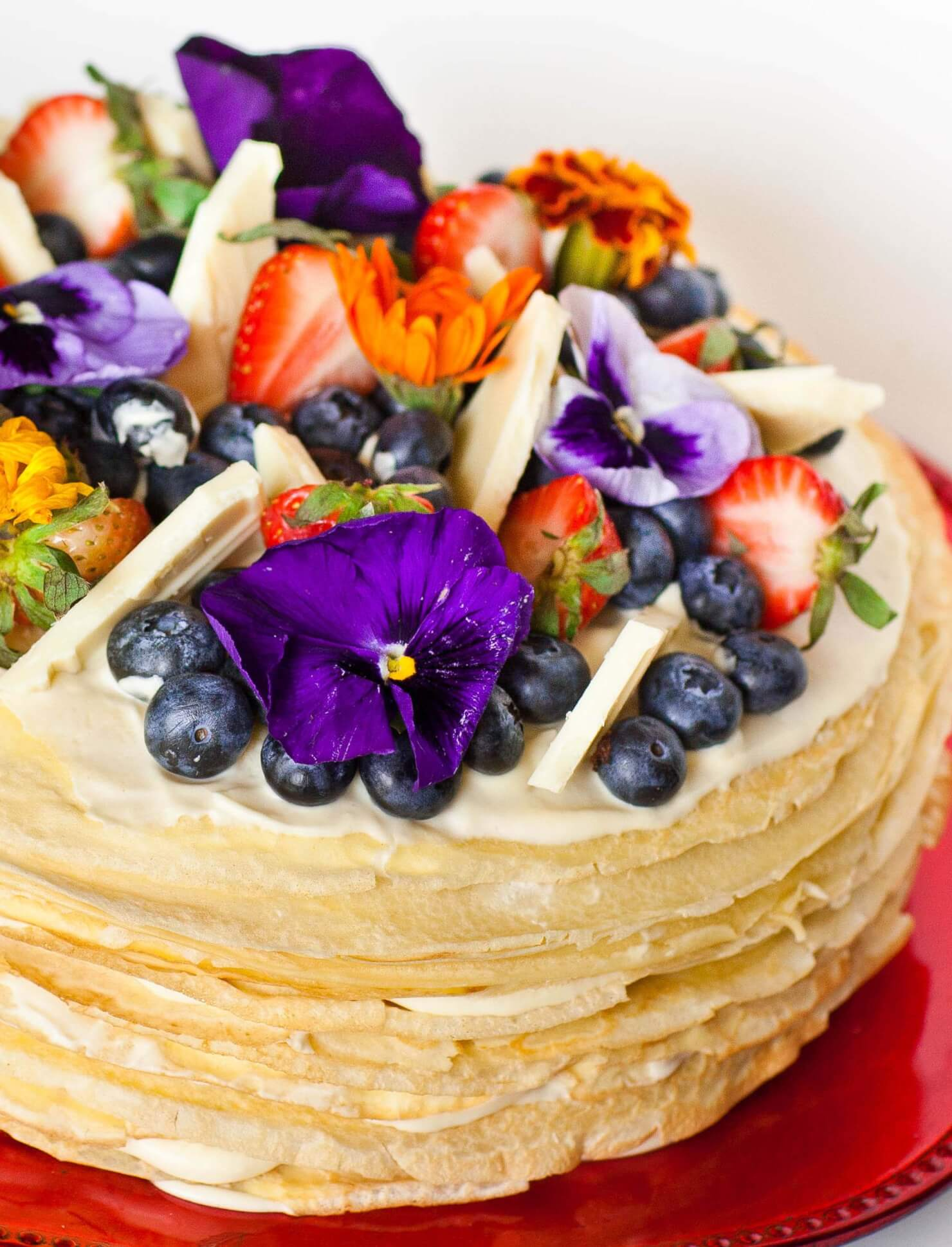 white chocolate crepe cake with edible flowers and berries