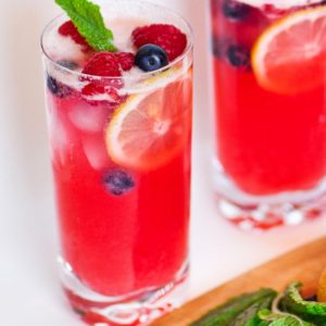 sparkling raspberry lemonade in tall glass with berries