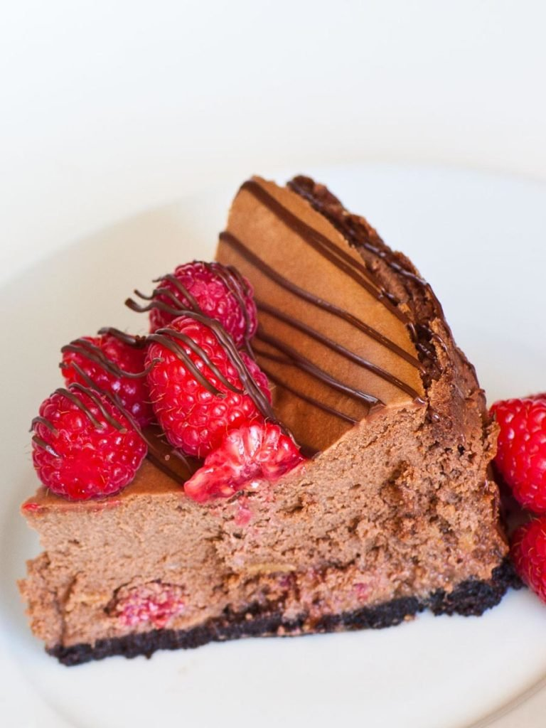 slice of caramel chocolate cheesecake topped with raspberries