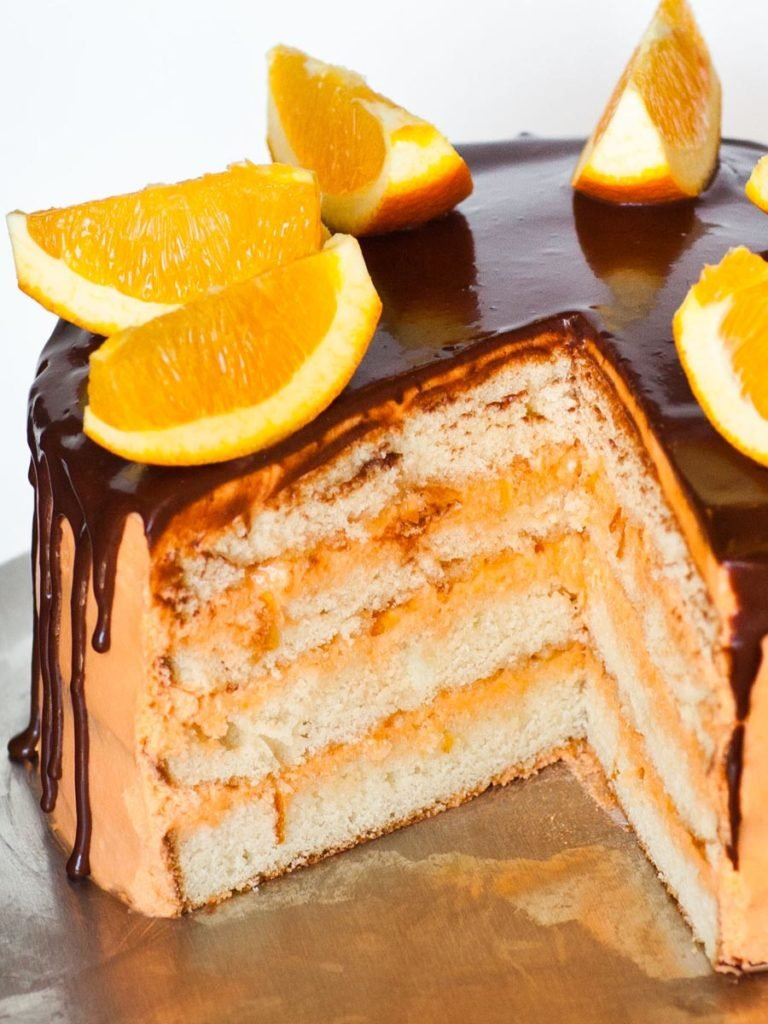 sliced orange cake with chocolate ganache, orange wedges and orange buttercream