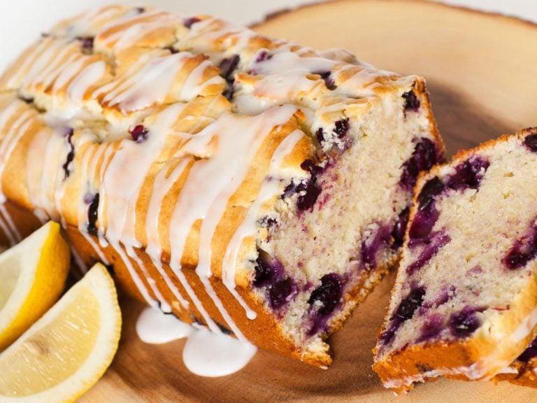 lemon blueberry bread with glaze and lemon wedges