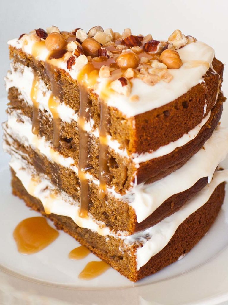 slice of pumpkin cake with caramel sauce and cream cheese frosting