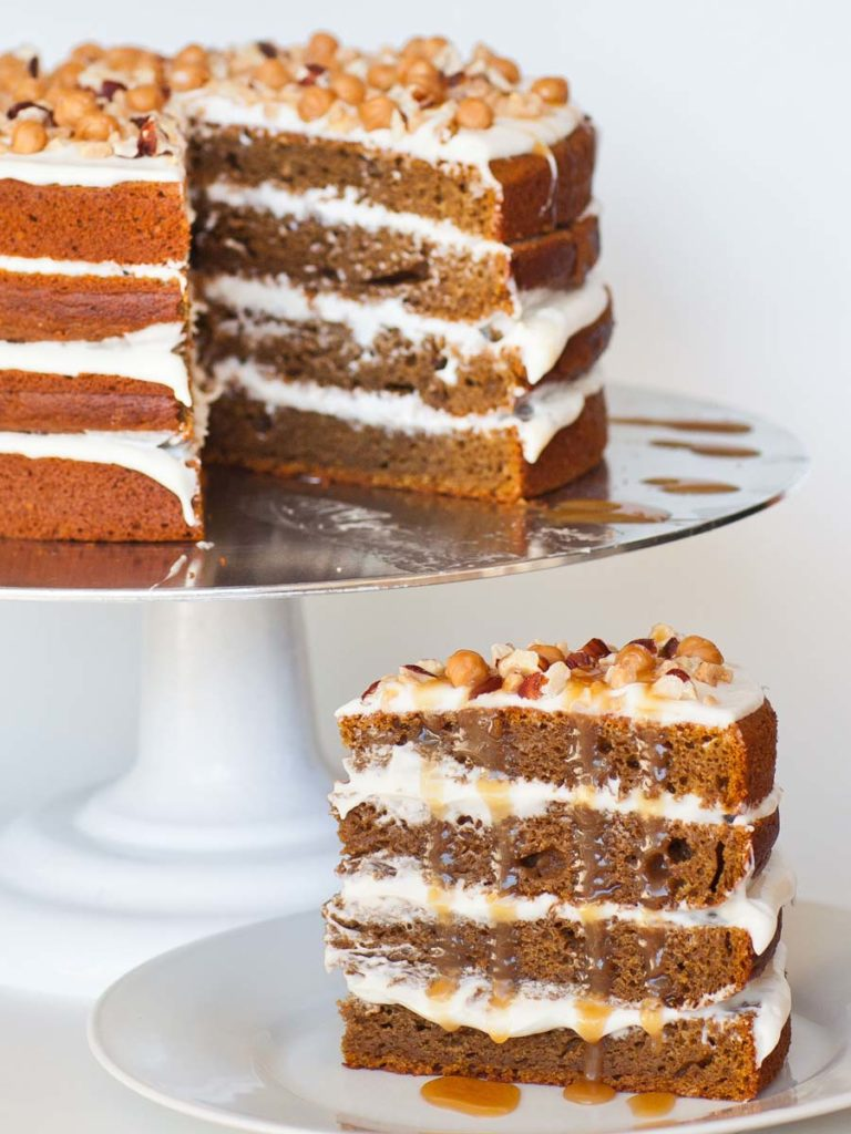 pumpkin spice cake slice, garnished with caramel bits and pecan nuts