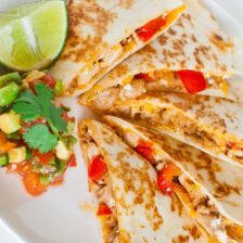 a plate full of chicken and pepper quesadillas, with lime and salsa