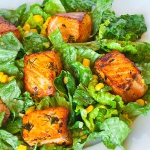 salmon chunks over avocado romaine salad with corn