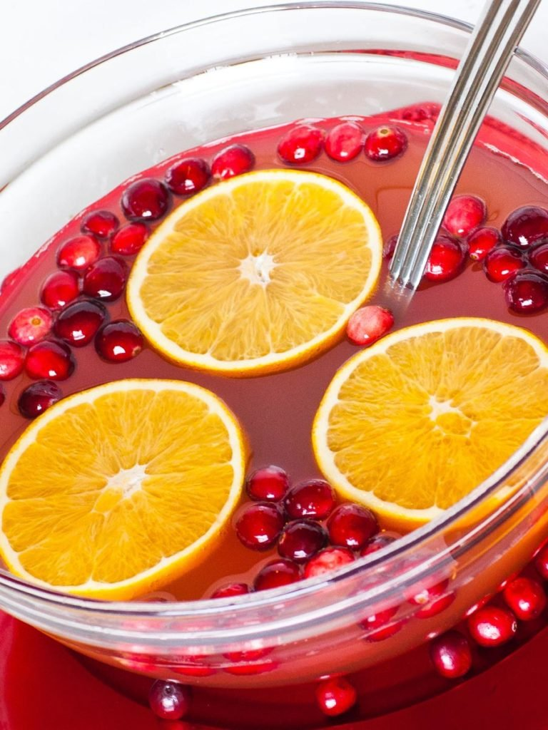 cranberry fruit punch in large bowl with oranges and cranberries