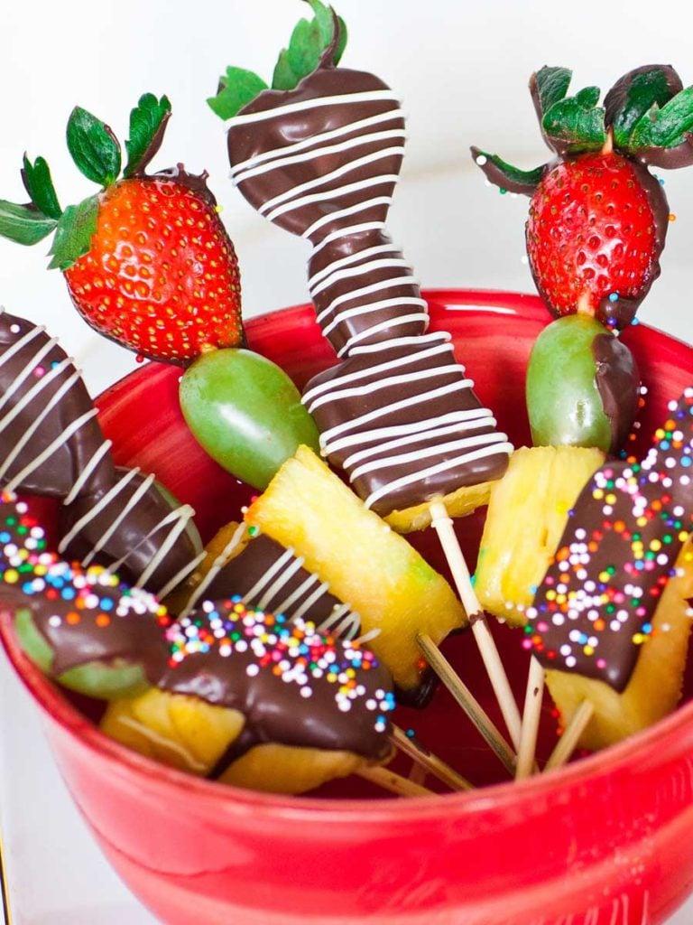 fruit skewers dipped in chocolate with sprinkles