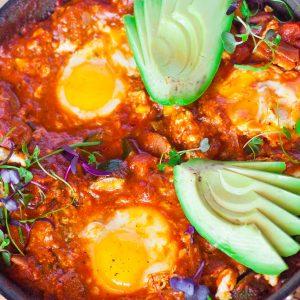 sausage shakshuka with eggs and avocado