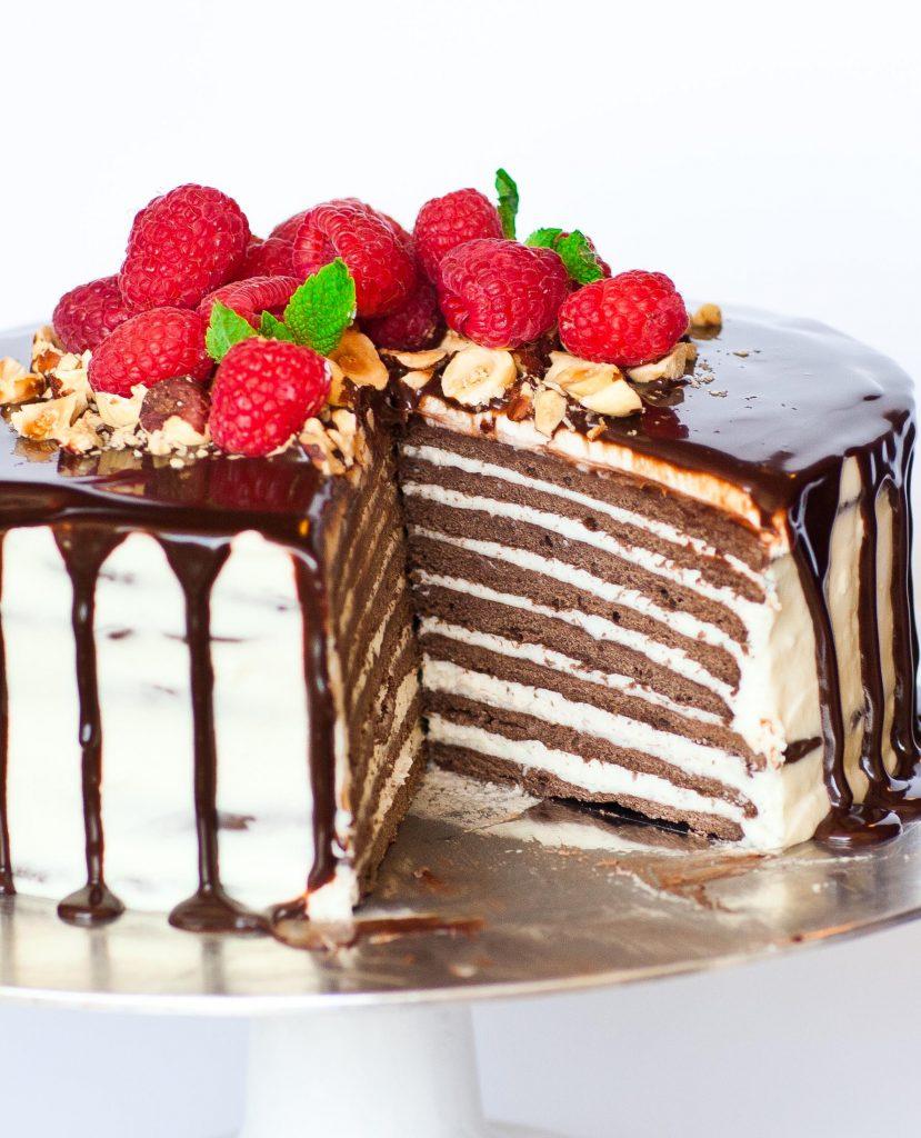 layered russian chocolate cake with ganache and raspberries