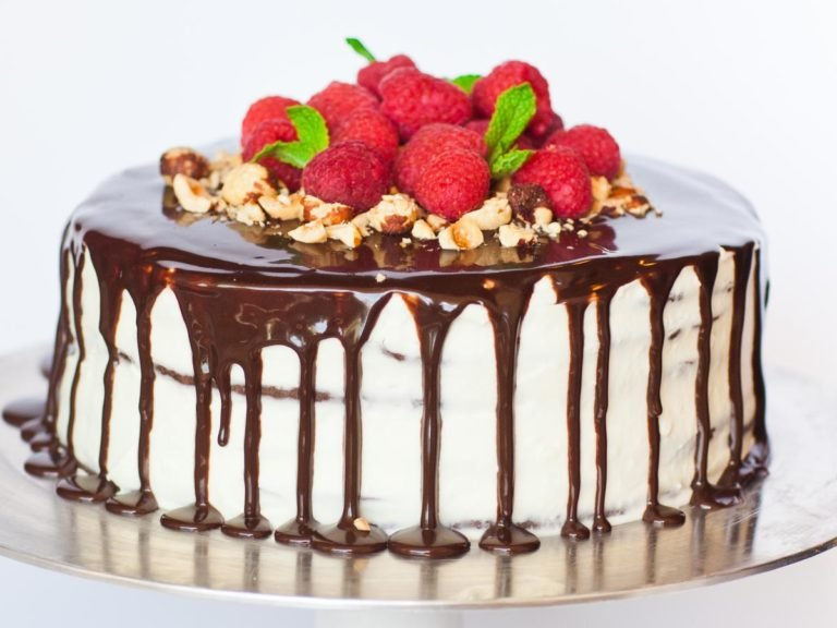 Chocolate Spartak cake topped with ganache and raspberries