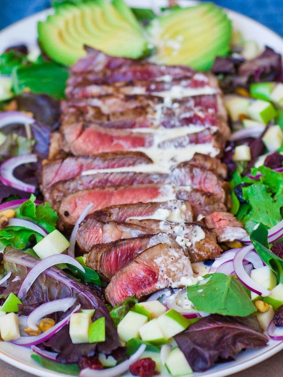 grilled ribeye steak over salad with blue cheese dressing