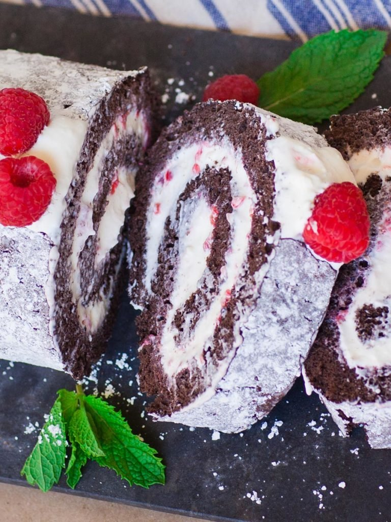 chocolate swiss roll with whipped cream frosting and raspberries