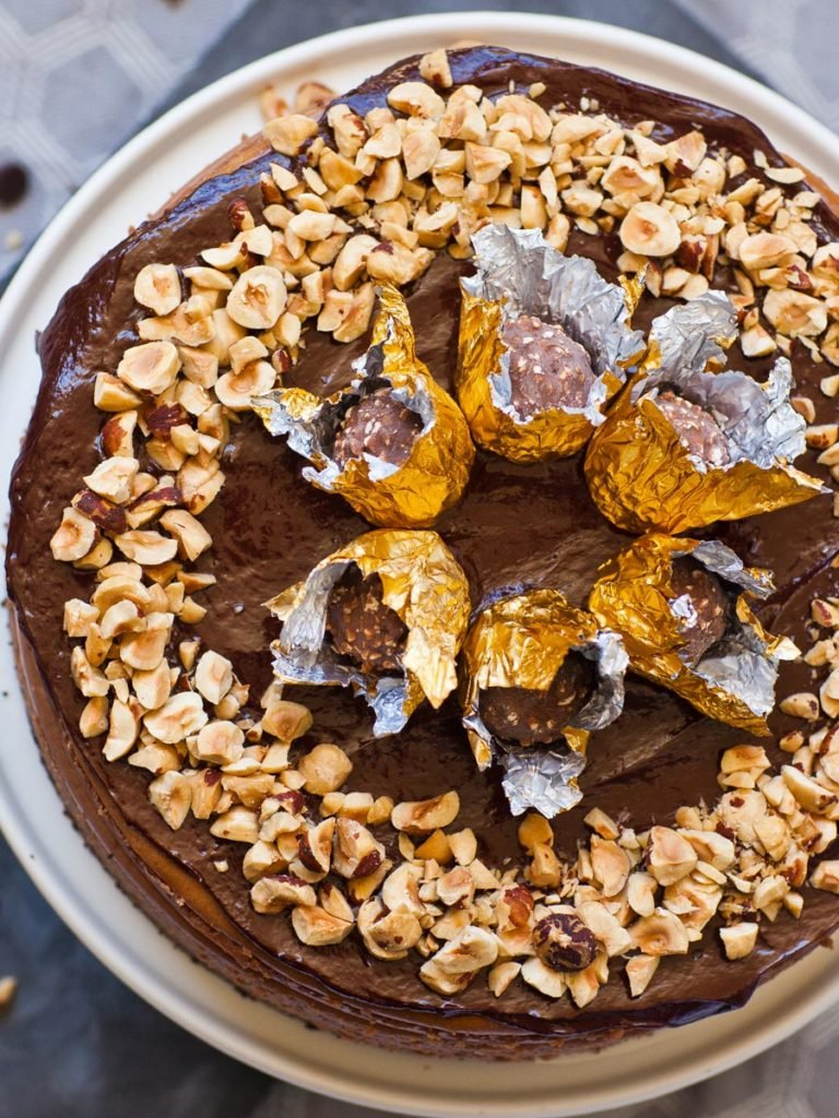 ferrero rocher chocolate hazelnut cheesecake topped with hazelnut and gold candy wrappers