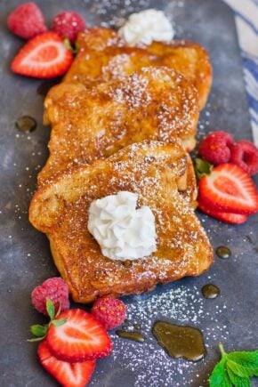french toast stuffed with nutella and served with maple syrup and berries and whipped cream