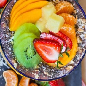 A close up of a smoothie bowl topped with fruit