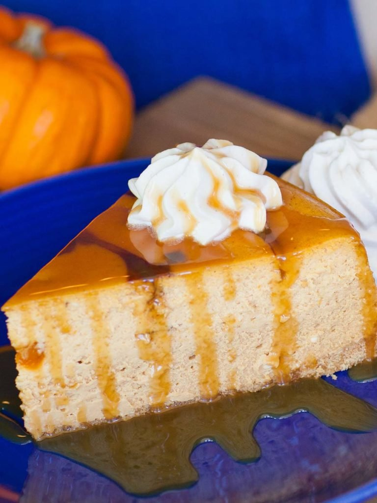 slice of caramel pumpkin cheesecake with caramel sauce
