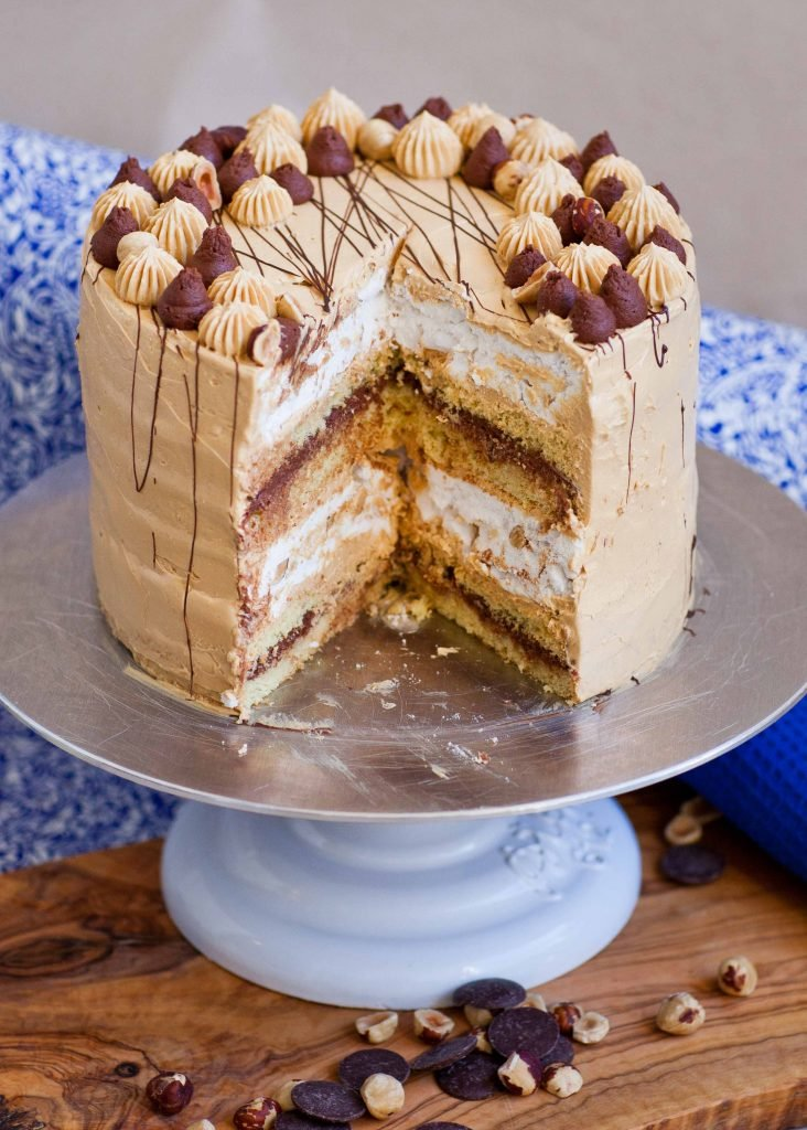 inside of kyiv cake with hazelnut meringue layers, caramel frosting and chocolate ganache on cake turntable