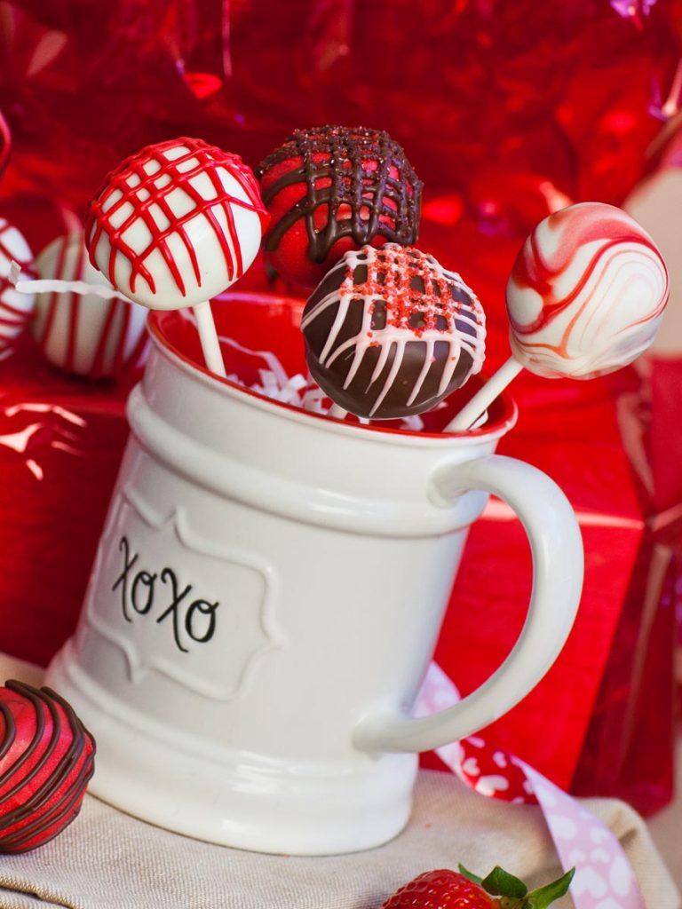 caramel cake pops dipped in chocolate in red coffee mug