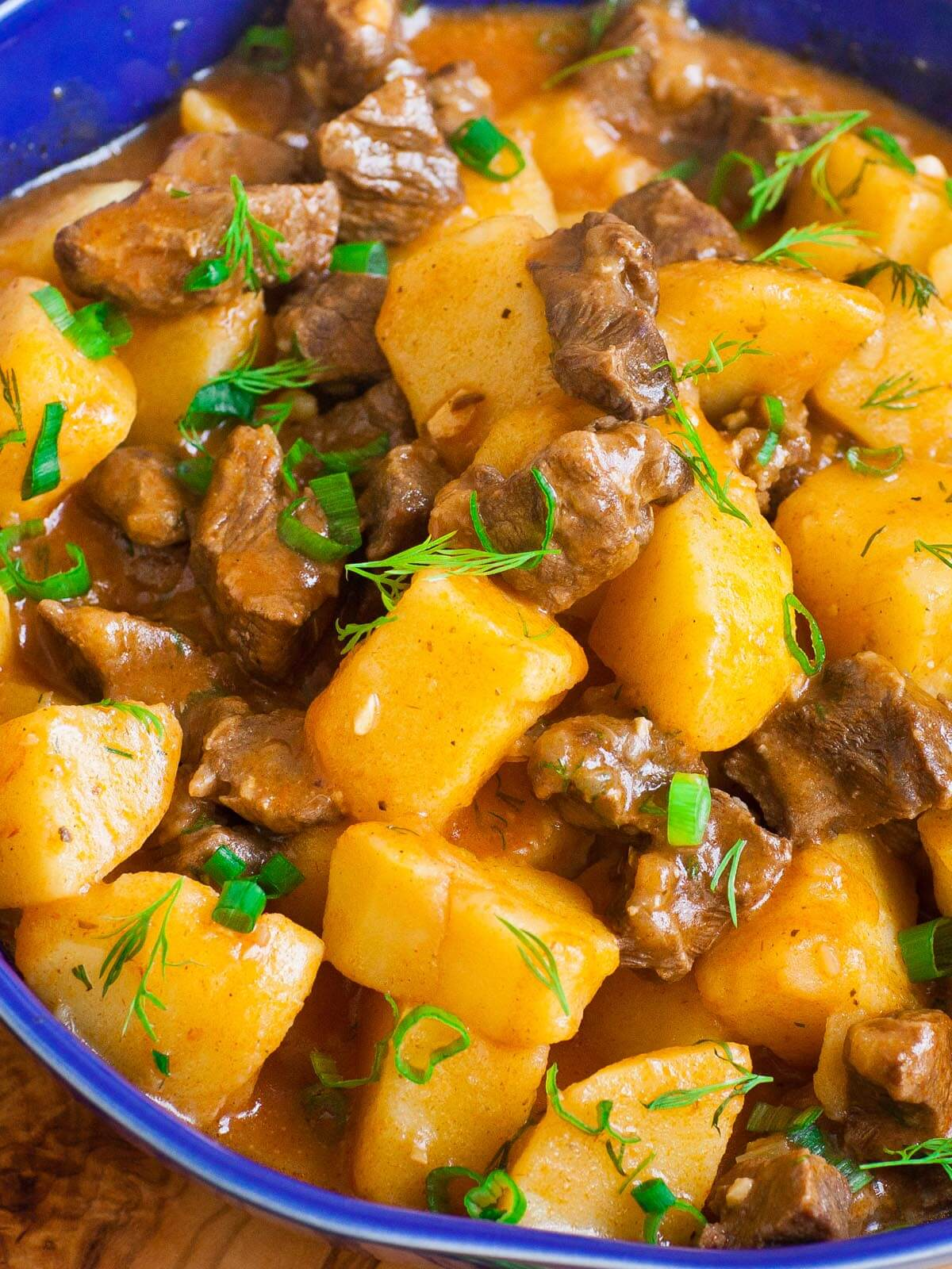 a bowl of beef stew with potatoes and dill