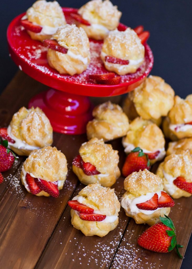 strawberry cream puffs on tray and cake stand