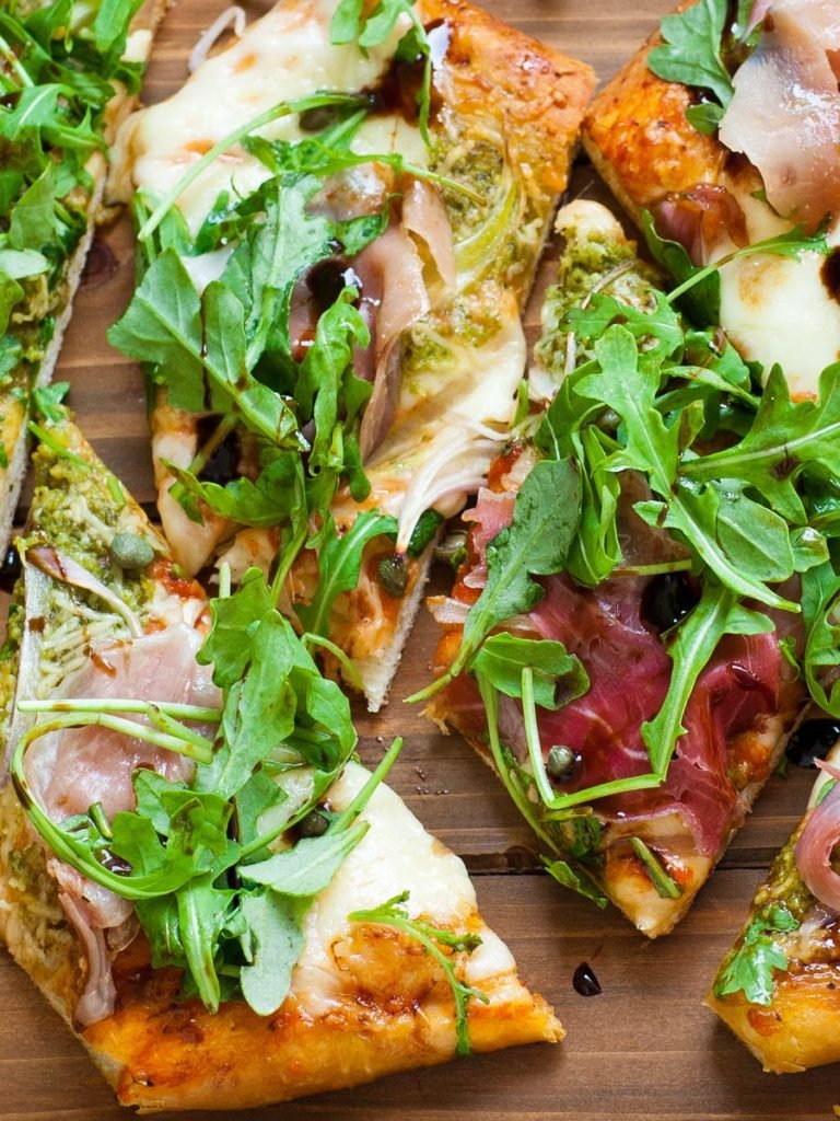 arugula prosciutto pizza with basil pesto and homemade pizza dough
