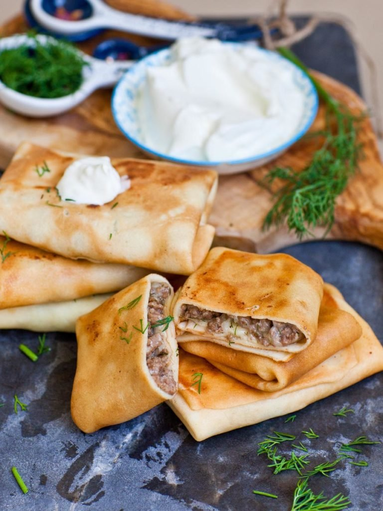 ukrainian cheese and beef filled blini with sour cream