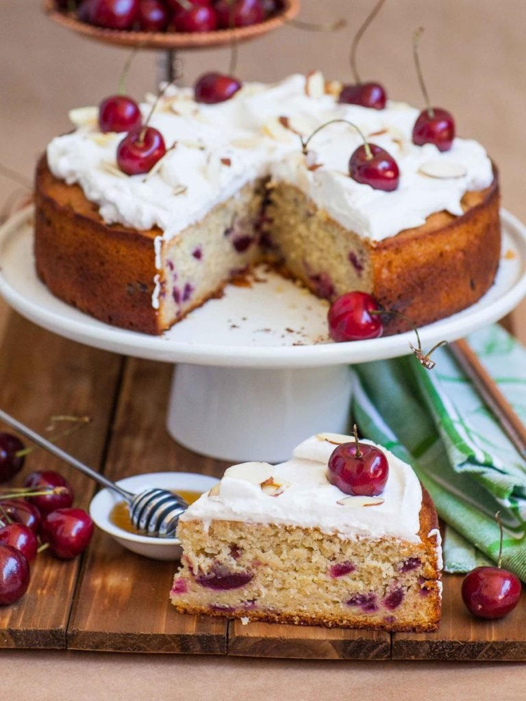 honey cherry cake with kirsch whipped cream and cherries on top