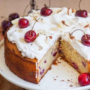 A sliced honey cherry cake on a cake stand with fresh cherries