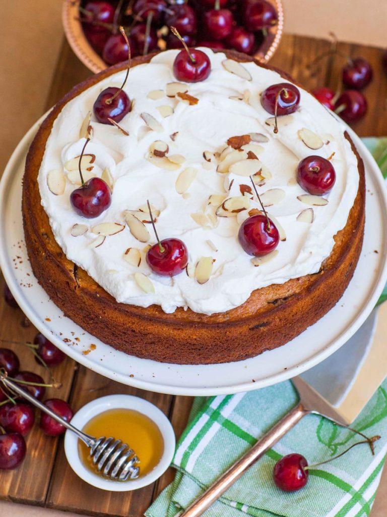cherry honey cake with cherry whipped cream and fresh cherries