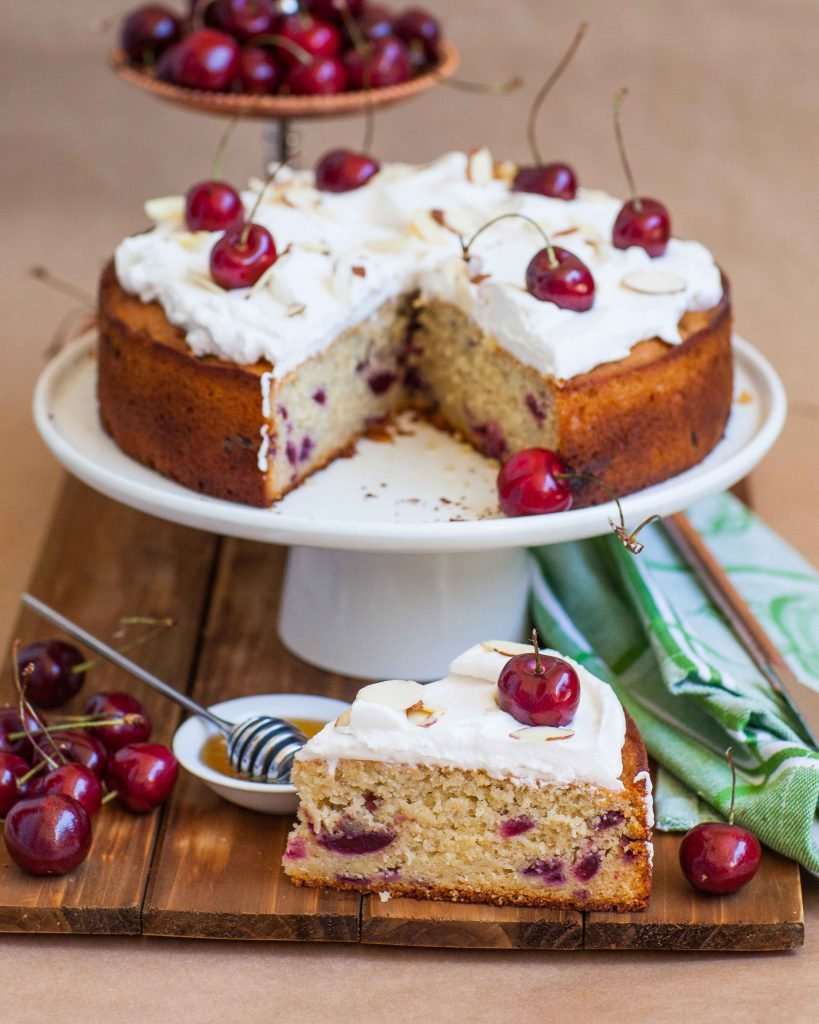 honey cherry cake slice with whipped cream frosting