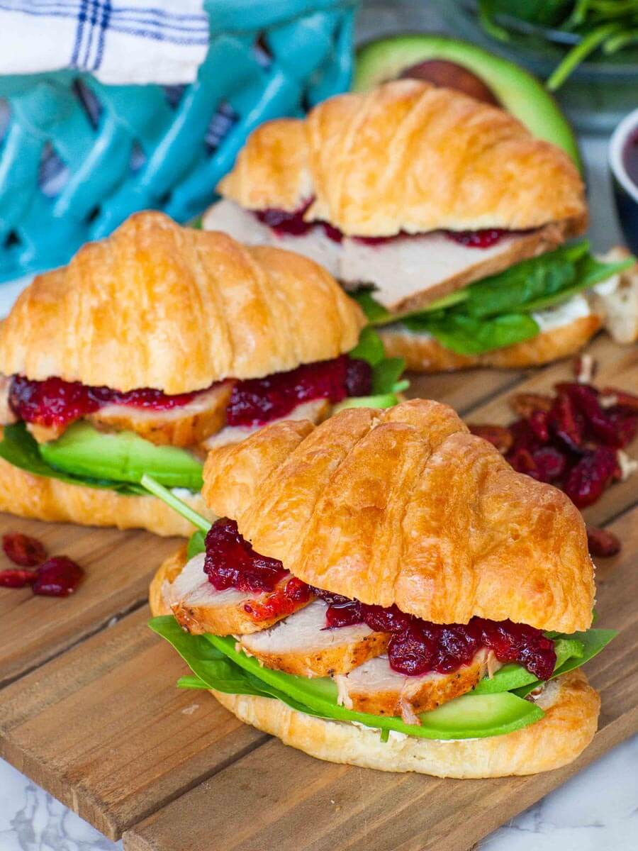 cranberry croissant sandwich with goat cheese spread, pork and avocado