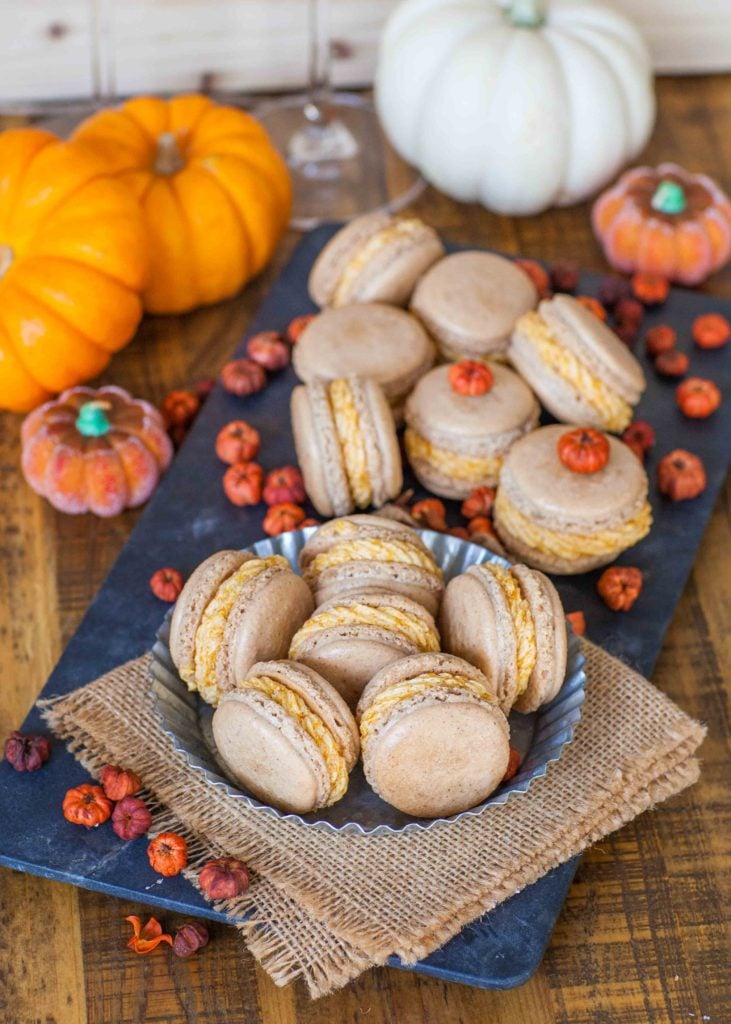 pumpkin spice macarons on slate board with small pumpkins