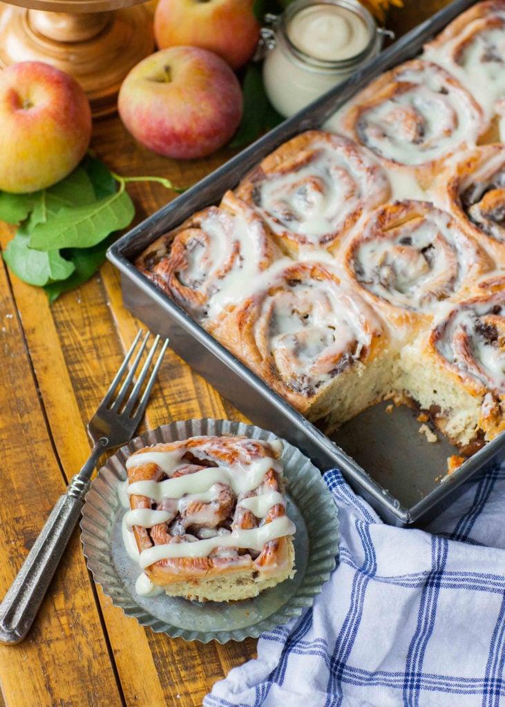 apple pie cinnamon rolls in pan with apples