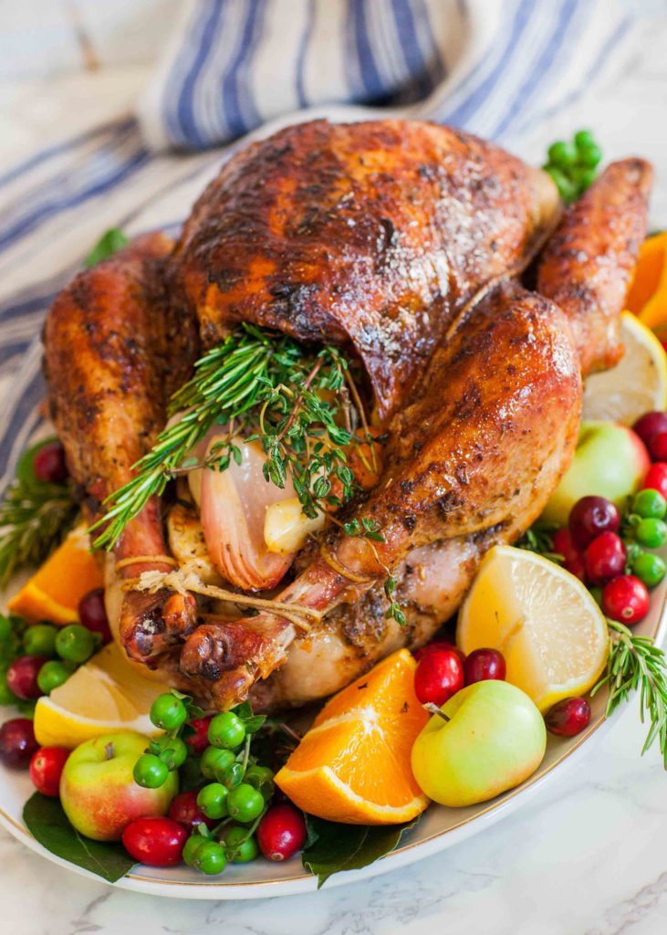 Thanksgiving turkey on platter stuffed with fresh herbs, oranges and apples