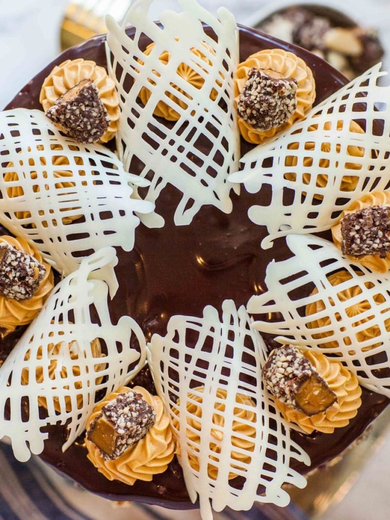 almond roca cake recipe garnished with white chocolate lace garnishes