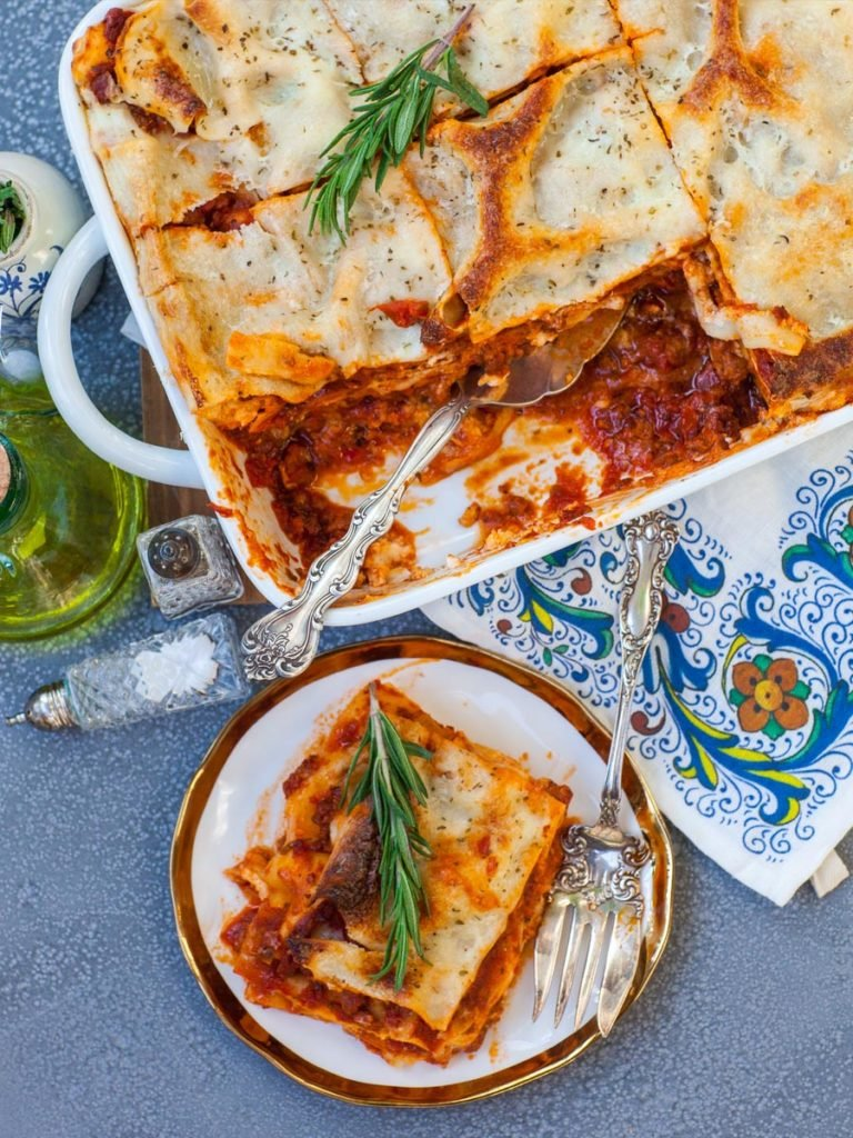 the best meat lasagna with cheese; slice of lasagna on gold plate