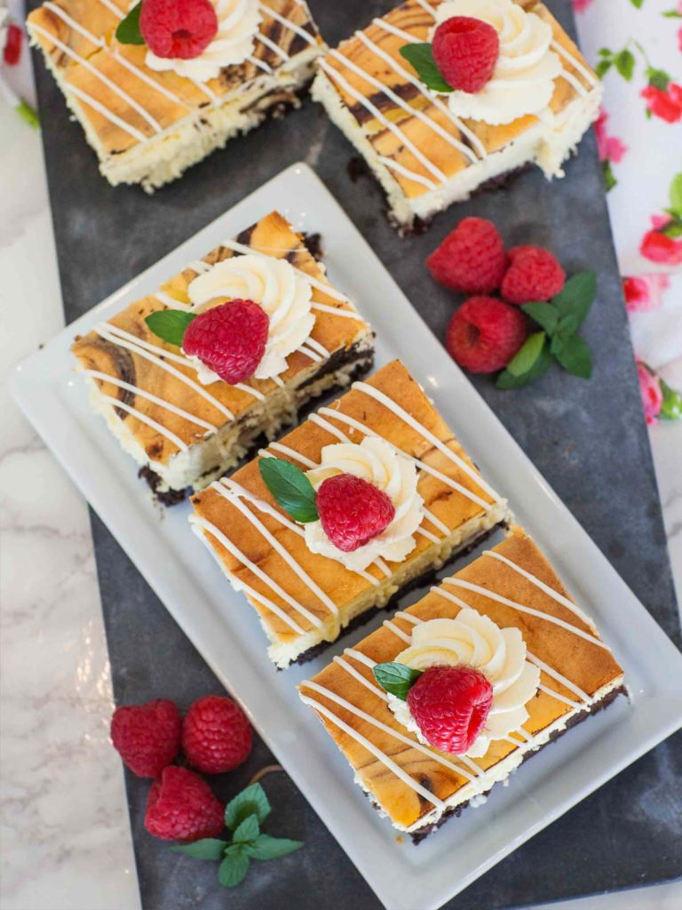chocolate cheesecake bars drizzled with white chocolate with raspberries