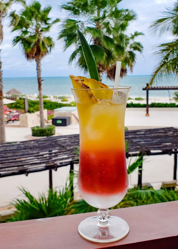 Layered Pineapple Cherry Drink with tropical view