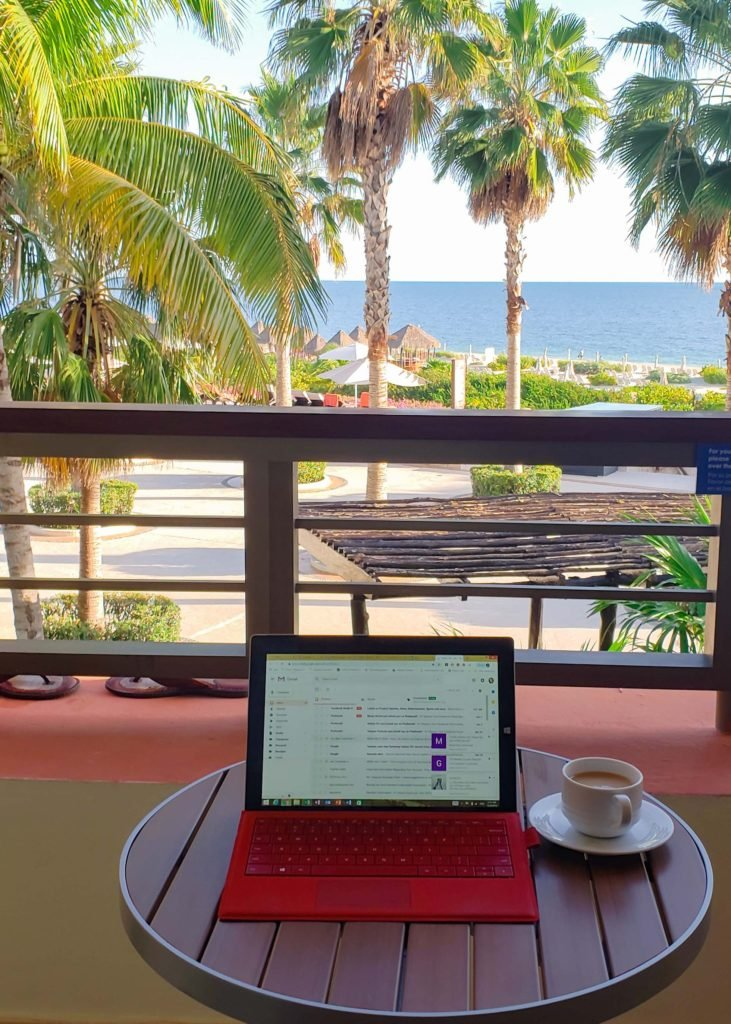 laptop on table with ocean view and palm trees