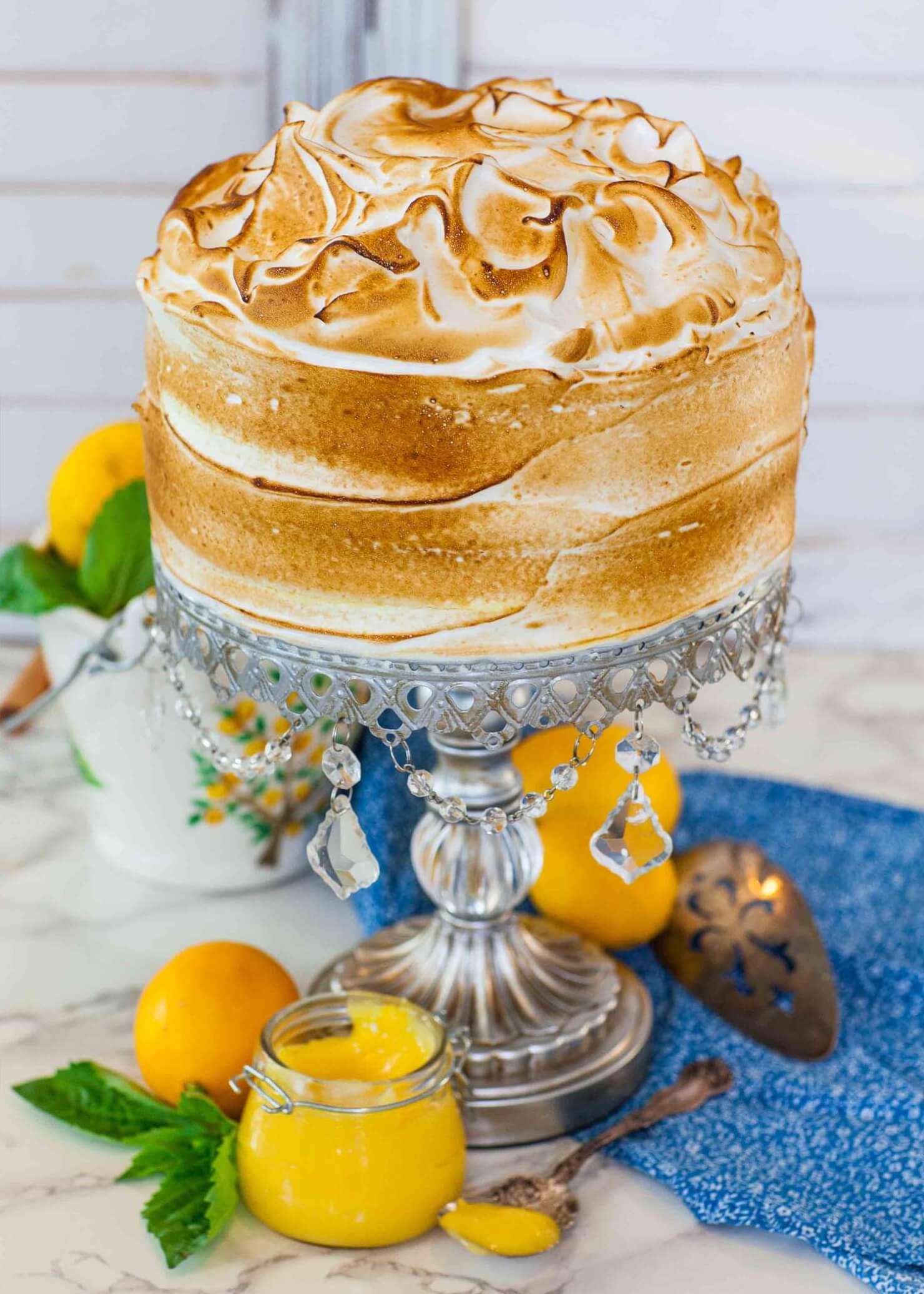 lemon meringue cake on rhinestone stand with torched meringue